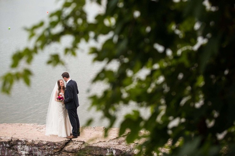 bride and groom cuddle together precariously on stone wall overhanging the river, on washington's landing in pittsburgh. bride laughing. photographed from far away with green trees in foreground.