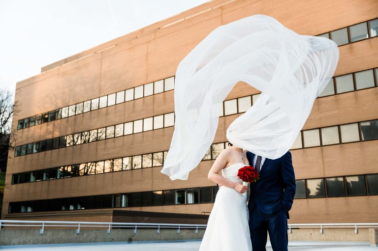 bride's cathedral length veil flies in the wind up over her head and covers her face