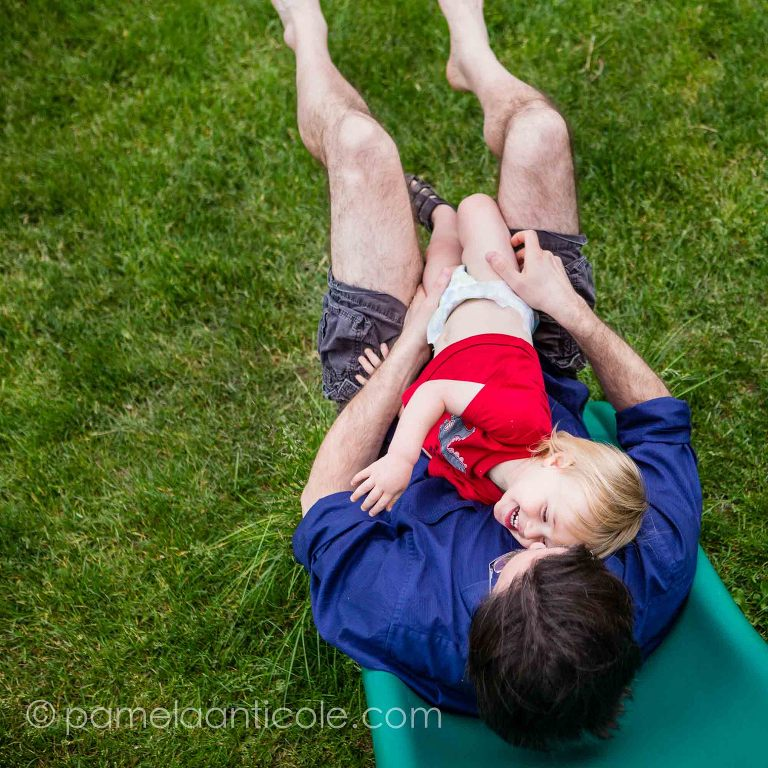 baby hugging daddy outside on slide, family joy documentary photography