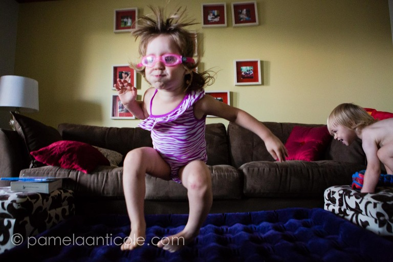 kids jumping off the sofa pretending to swim on the floor documentary photo