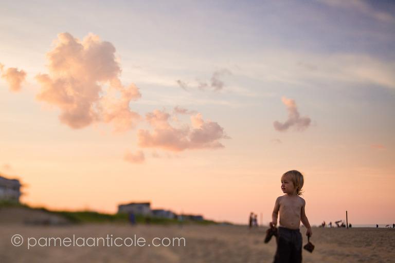 young boy on sandbridge beach at sunset