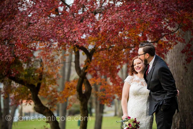 bride and groom laugh together in allegheny cemetery, in front of a red tree in the autumn