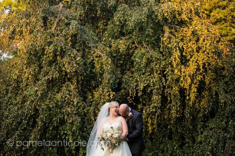 groom stands behind bride and kisses her shoulder, bride laughs. standing in front of a tall green bush lit beautifully with sunset light