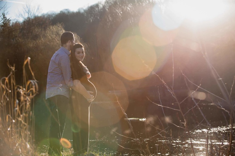husband cuddles with pregnant wife overlooking lake with sunset sun flare across image, wife looking at camera