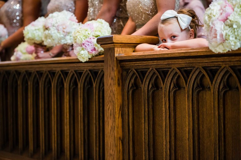 flower girl rests her head on her hands, half asleep during wedding ceremony while surrounded by bridesmaids at church.