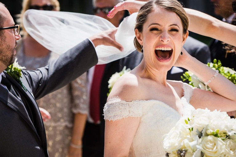 bride's veil flying in the wind, laughing with mouth wide open, as hands fly in to restrain veil