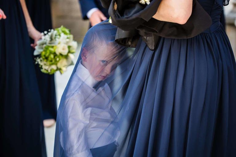 disgruntled ring bearer hiding under bridesmaid's dress, giving bored look