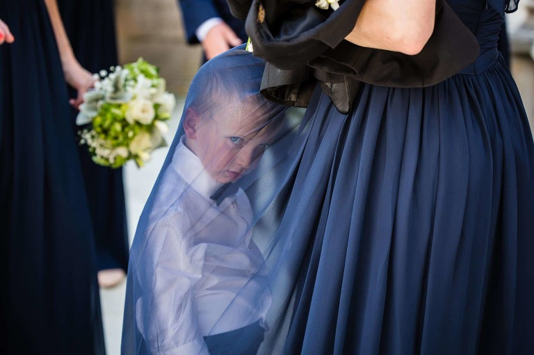 disgruntled ring bearer hiding under bridesmaid's dress, giving bored look