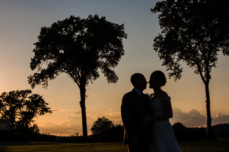silhouette of bride and groom at sunset surrounded by trees, on oakmont country club golf course