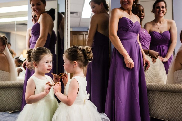 cute flower girl looking at herself in the mirror, with a pretzel, in the bridal suite at heinz chapel, before the wedding ceremony begins