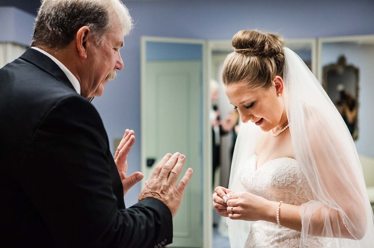 bride wearing veil receiving a surprising gift from her dad right before her heinz chapel wedding ceremony