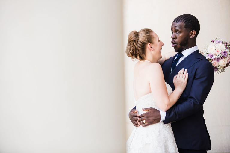hilarious moment between a young bride and her emotional groom during their photoshoot at the architectural columns at the mellon building in oakland, pittsburgh pa