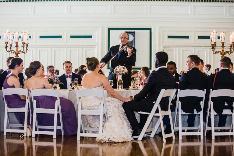violinist serenades a bride and groom while their wedding party, bridesmaids, groomsmen, family, and friends look on at their wedding reception at the unique pittsburgh venue soldiers and sailors