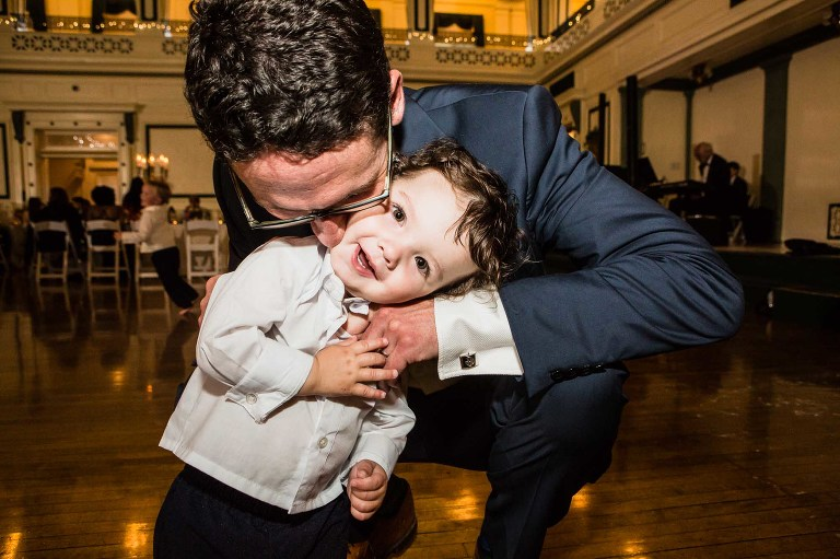 adorable photograph of a little ring bearer being hugged by his dad at his aunt's wedding reception at the unique pittsburgh wedding venue soldiers and sailors