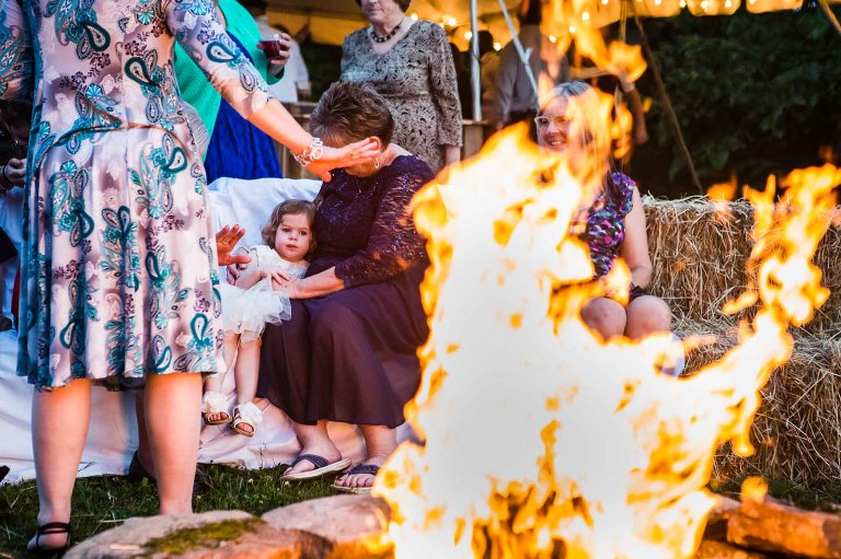 wedding guests snuggle around the late night bonfire at the reception