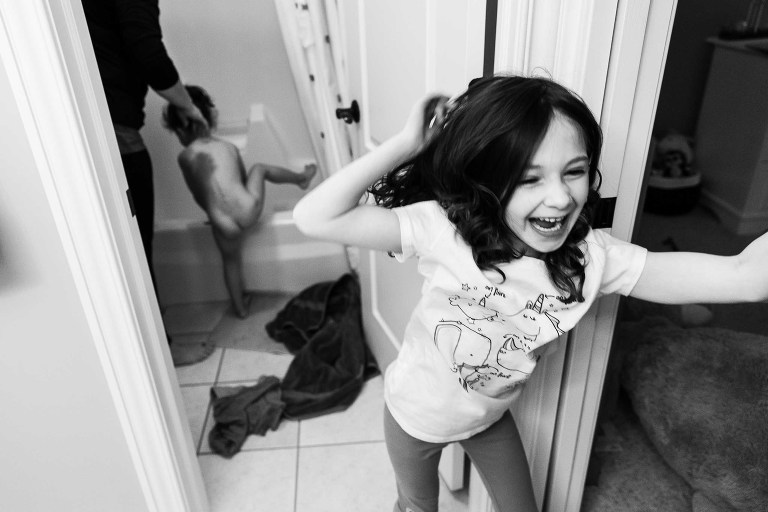 black and white photo of little girl laughing running out of bathroom where mom is with little sister