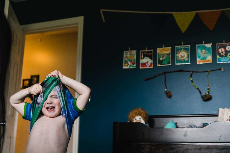 little boy struggling to get dressed, pulling his pajamas over his head and getting stuck
