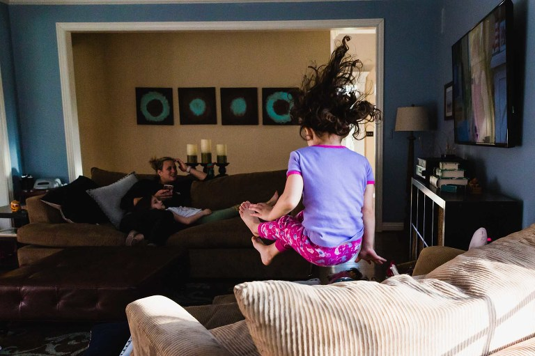 little girl jumping on living room chair while watching tv, hair flying