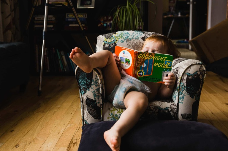toddler reading book in small chair, lounging with leg over arm of chair