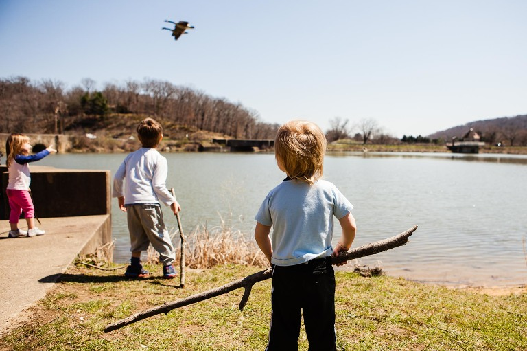 3 little kids playing with sticks and watching birds fly over a lake