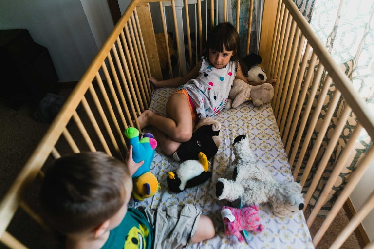 girl lounging in crib with lots of stuffed animals