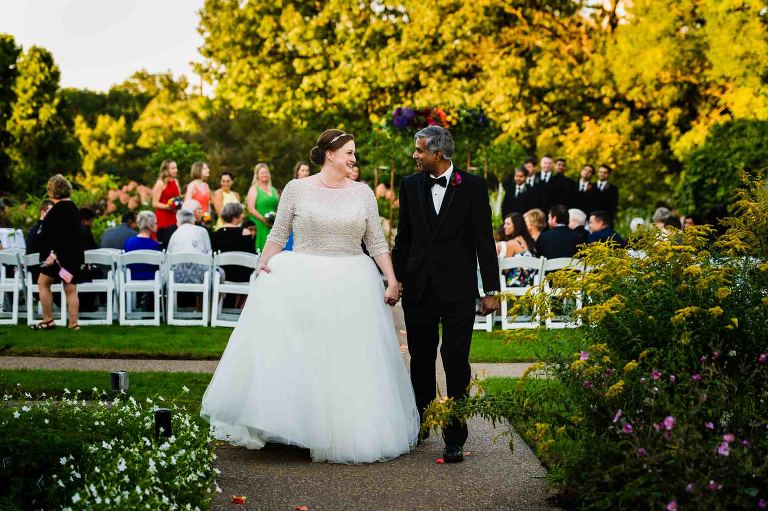 bride and groom recessional smiling at each other, guests behind them at phipps conservatory
