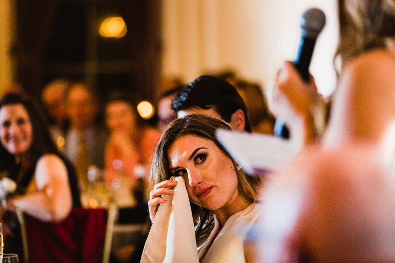 bride uses her napkin to wipe tear out of her eye, during speeches