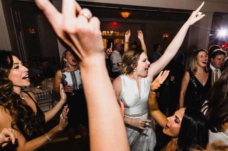 bride dances wildly with her guests, fingers in air