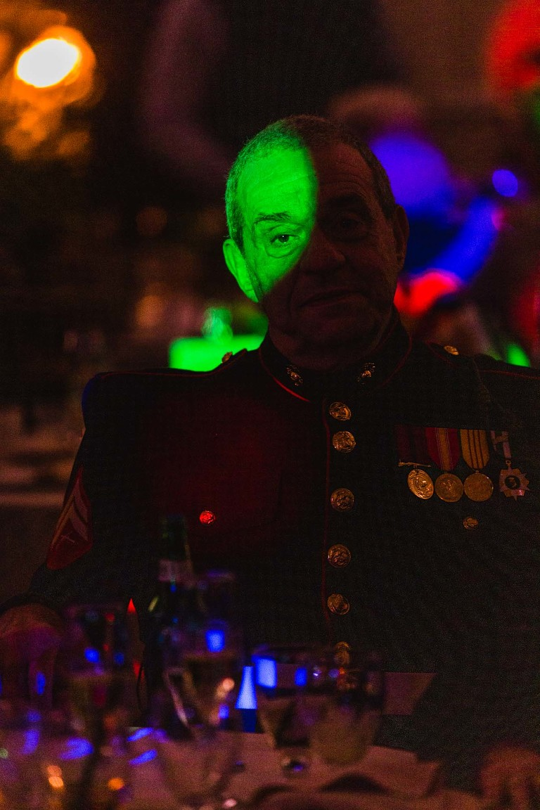 portrait of elderly man in military attire in dark room, spotlit by colorful dj lights