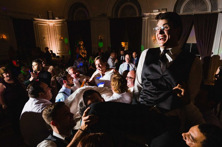 groom lifted up on chair during wedding reception, surrounded by cheering guests