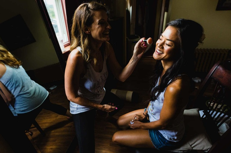 asian bride getting makeup applied by her friend