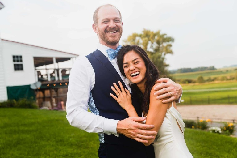 smiling groom hugs bride into his chest and they laugh together, surrounded by farm