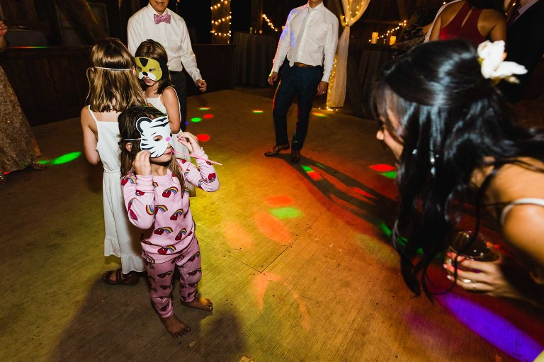 little girl in pajamas wears mask on wedding dance floor with lights flashing, looks up at bride