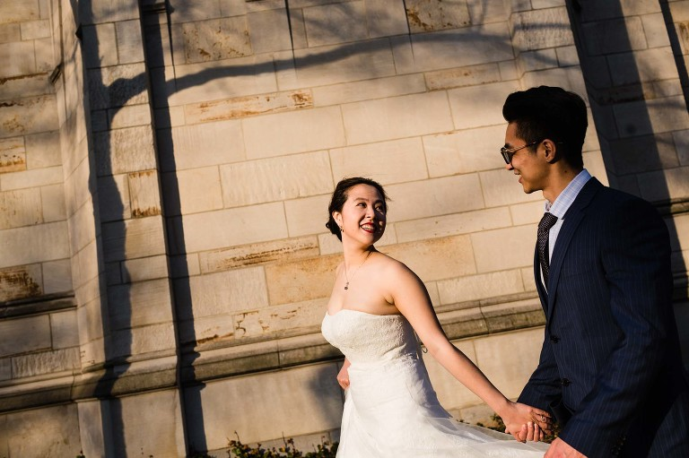 bride leads groom, holding hands in the sun, walking in front of an old building the cathedral of learning