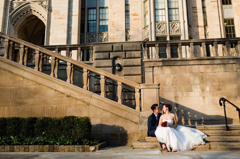 bride and groom snuggle up together, seated at the bottom of stairs at pitt's cathedral of learning, in beautiful golden light at sunset.