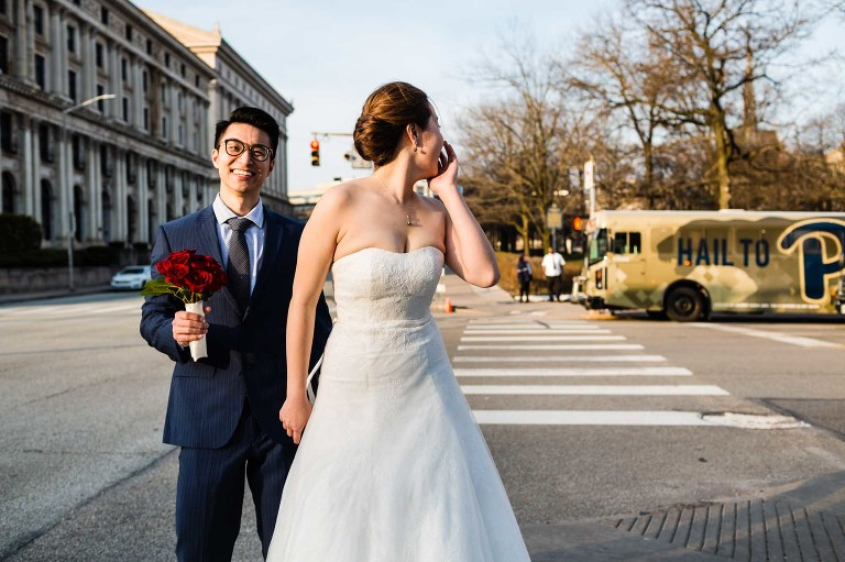 bride and groom pause on a street corner to laugh back at the scene behind them, in a casual candid moment