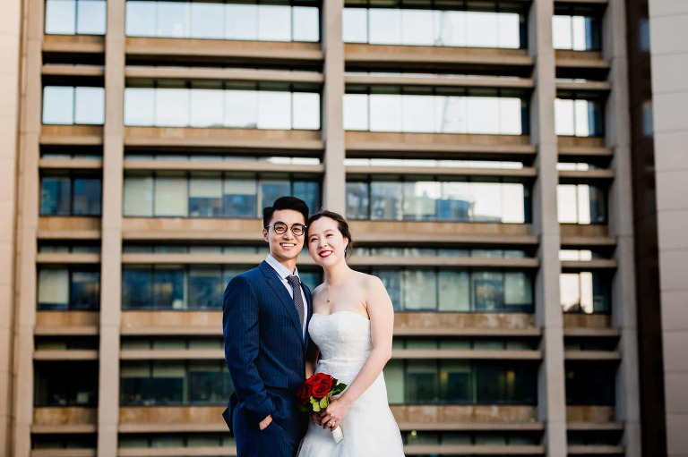 bride and groom pose for the camera in a parking lot in oakland, in front of a tall building on pitt campus