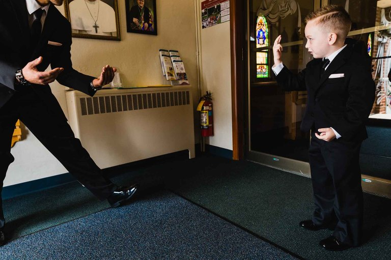 groom wrestles with his ring bearer on his wedding day, in the church vestibule.