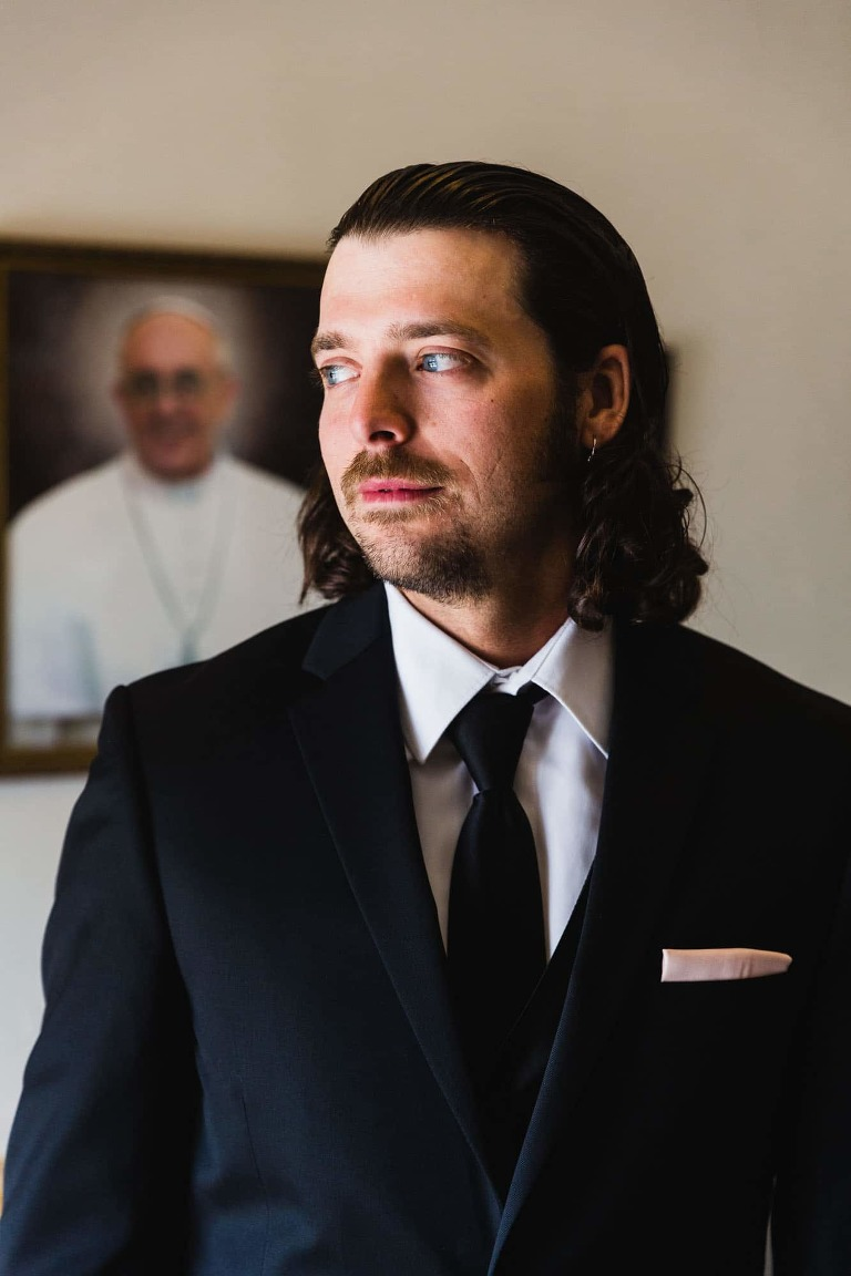 portrait of the groom photographed on his wedding day in front of a picture of the pope.