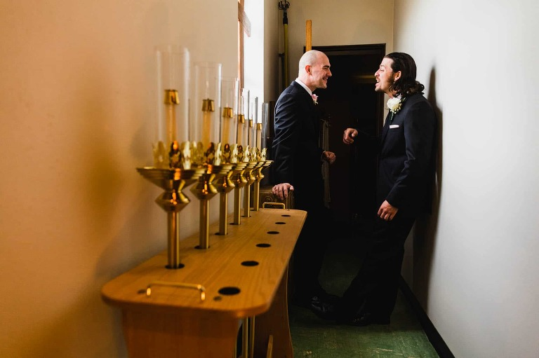 groom and his best man share a moment laughing together in the church vestibule, before their wedding at st. vitus church in new castle, pa