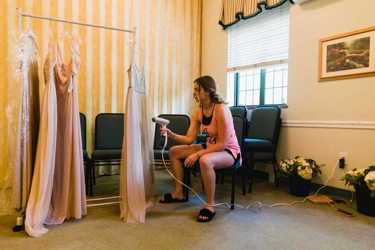 bridesmaid prepares the bridesmaid dresses with steam cleaner, before wedding ceremony, in church basement at beverly heights presbyterian in mount lebanon, pa