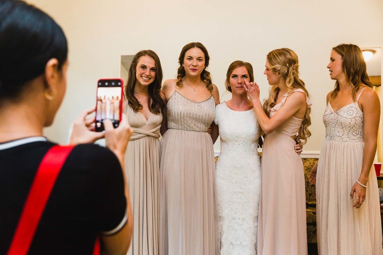 bride and bridesmaids check each other for perfection, before being photographed together. bridesmaid wipes something off bride's face.