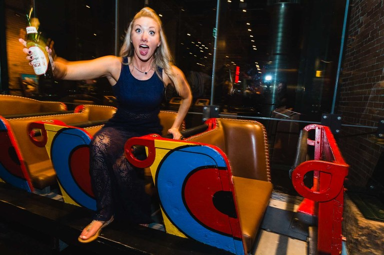 bridesmaid having fun at heinz history center wedding reception, laughing and goofing off in the kennywood racer car for a photograph
