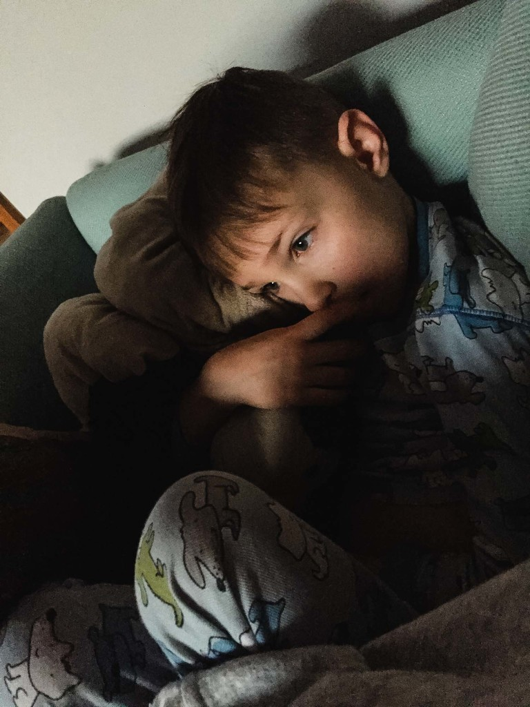cell phone photograph of little boy sitting in a chair in pajamas, moody light across his eyes and a pensive mood, with hands by his mouth.