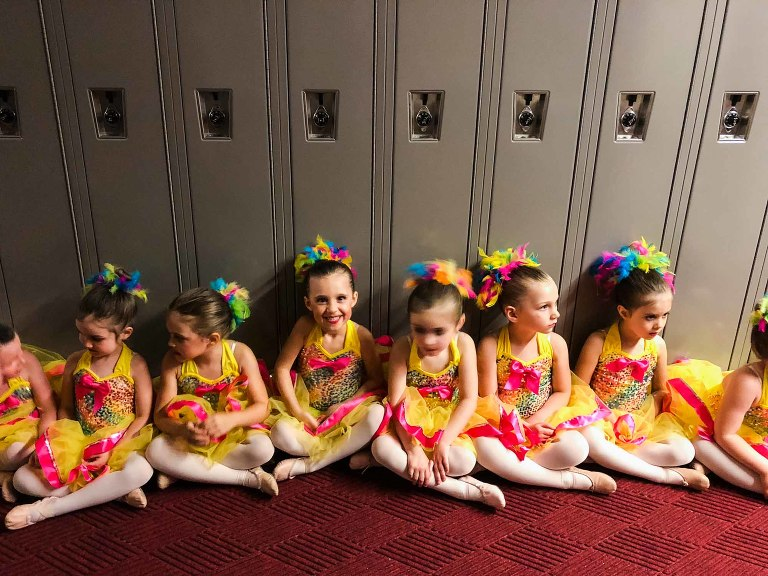 ballerinas lined up ready to go on the stage, in yellow and pink tutus, seated in front of a row of school lockers