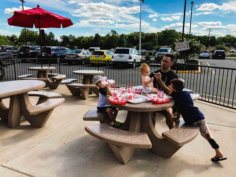dad and three kids sit at a concrete picnic table outside a fast food restaurant, surrounded by parking lot, feeding a baby sitting on the table