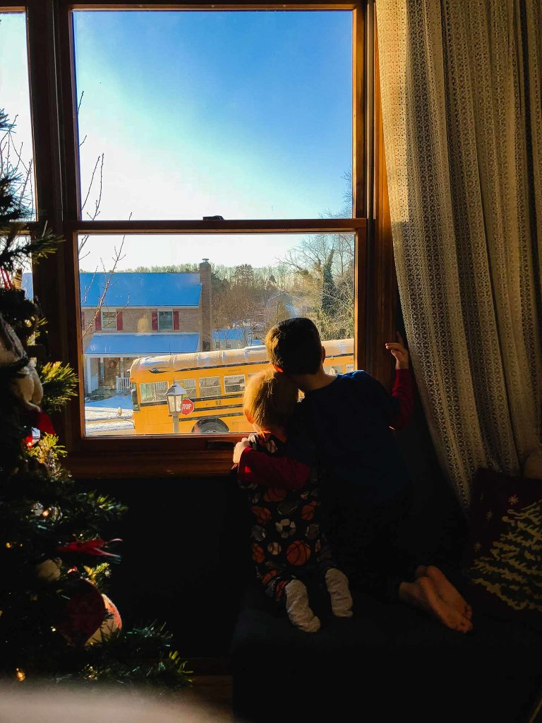 little boy and baby crawl up on bench and watch their big brother leave for school on the bus. they hug each other as they watch the bus drive by.