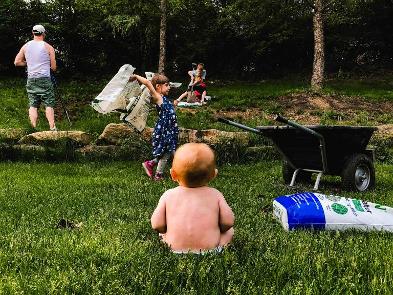 naked baby sits in grass watching family do yardwork in the yard beyond