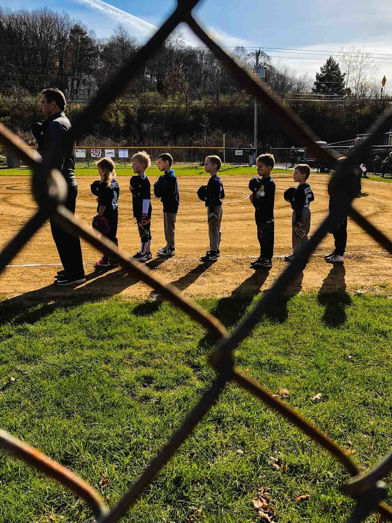 baseball team lined up for the anthem, as photographed through the chain link fence