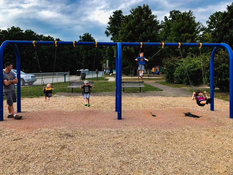four siblings swing on four swings on a swingset, watched over by father standing nearby smiling